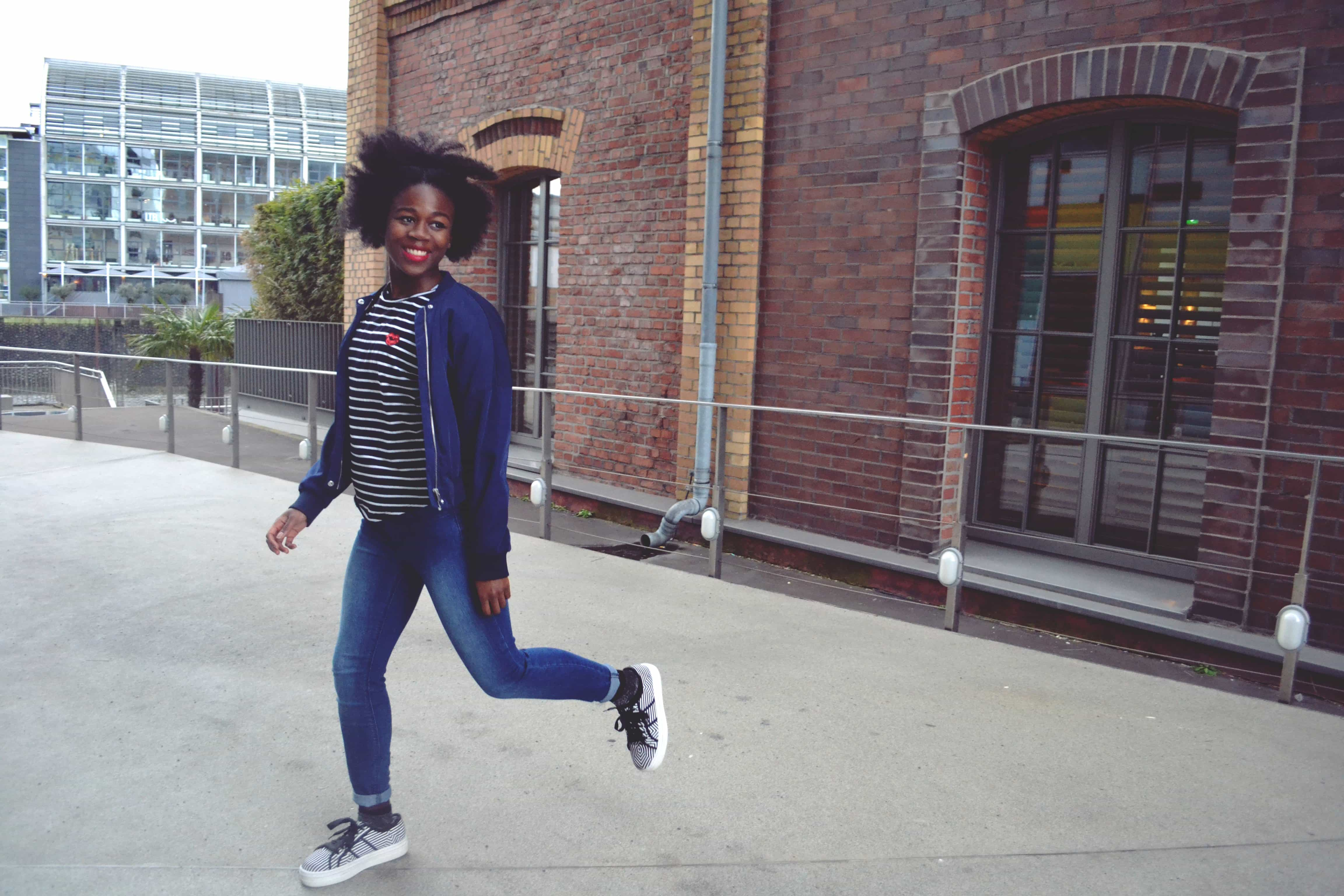 A woman with an afro wearing a navy blue bomber jacket, a black and white stripy t-shirt, blue skinny jeans and black and white stripy platform shoes jumps across the picture with a smile on her face