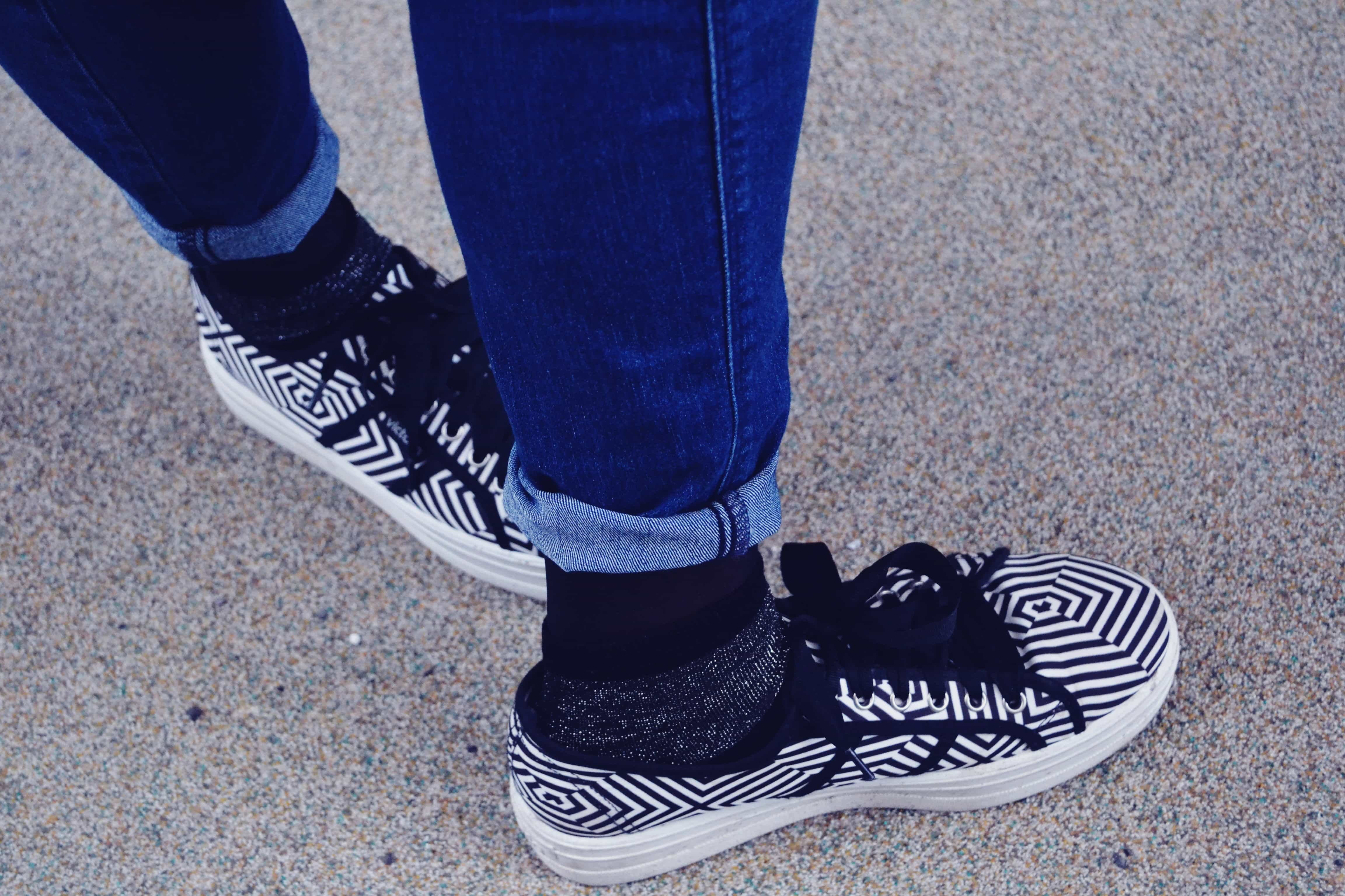 Close-up showing rolled up blue skinny jeans, glittery black socks and black and white stripy platform shoes.