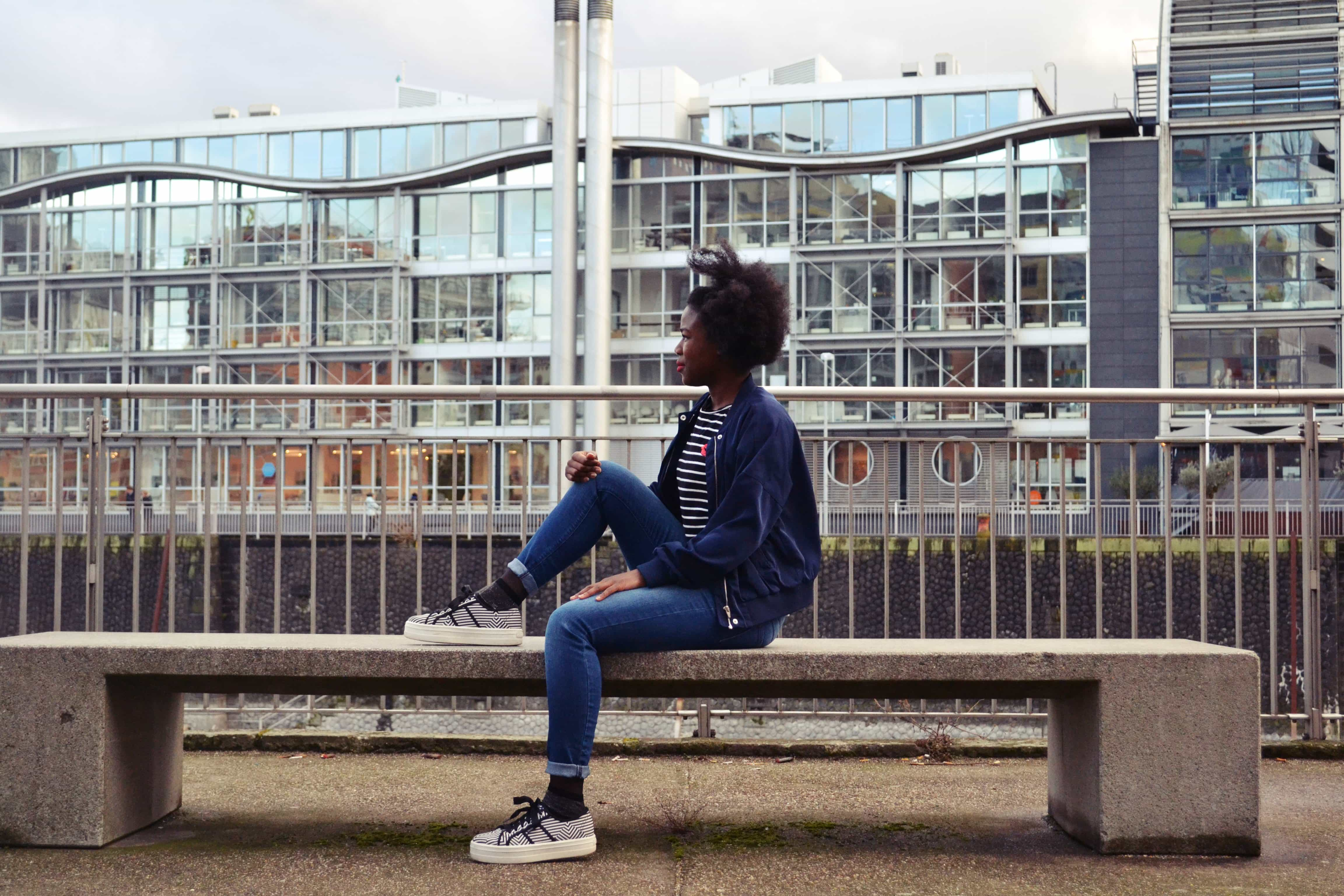 A woman with an afro wearing a navy blue bomber jacket, a black and white stripy t-shirt, blue skinny jeans and black and white stripy platform shoes sits sideways on a stone bench, looking away from the camera, with one foot placed on the bench.