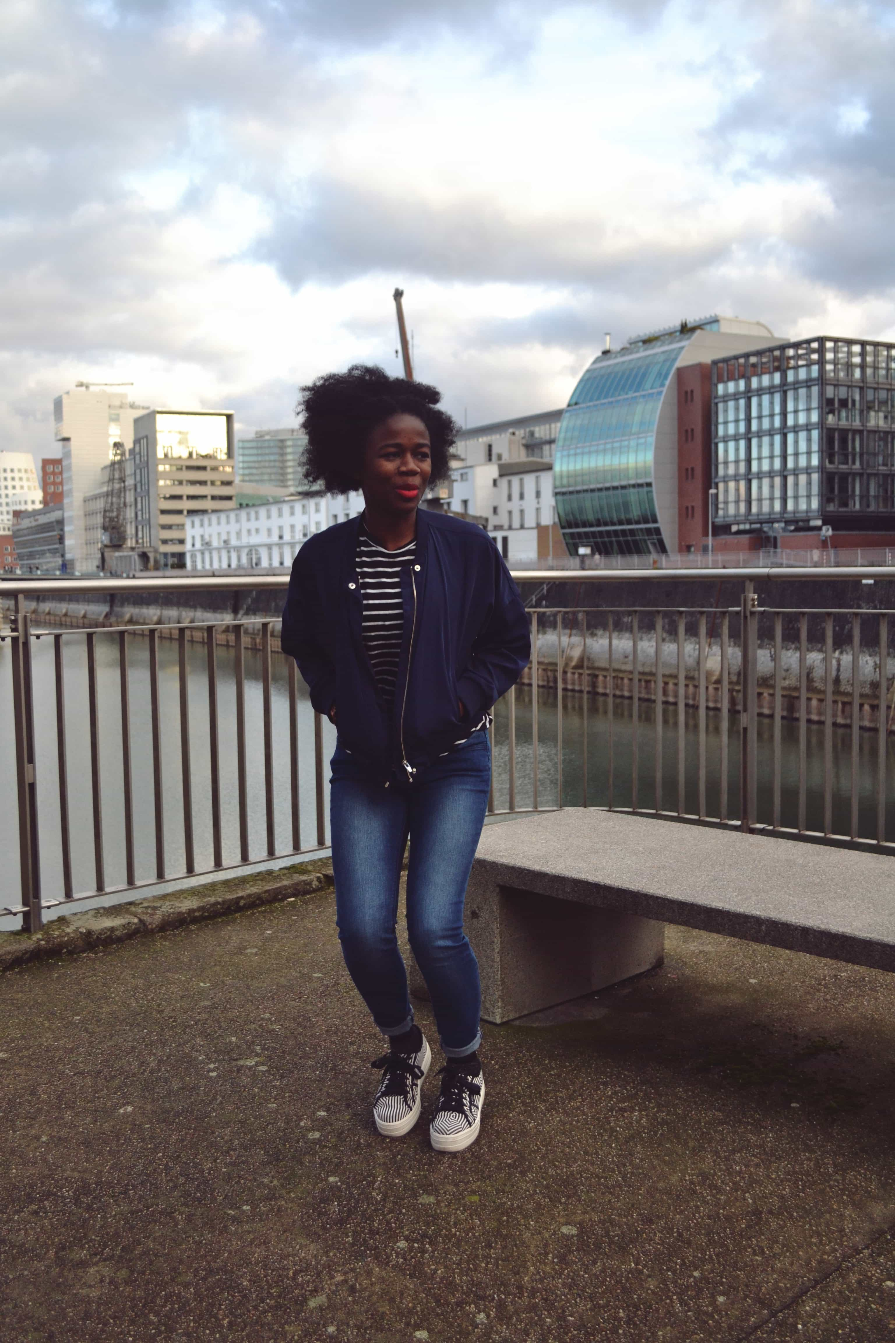 A woman with an afro wearing a navy blue bomber jacket, a black and white stripy t-shirt, blue skinny jeans and black and white stripy platform shoes lands on the floor, looking away from the camera, with city buildings and a blue sky in the background.